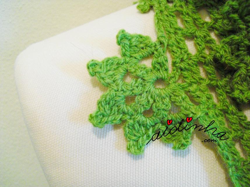 Pormenor da flor da gola de crochet verde