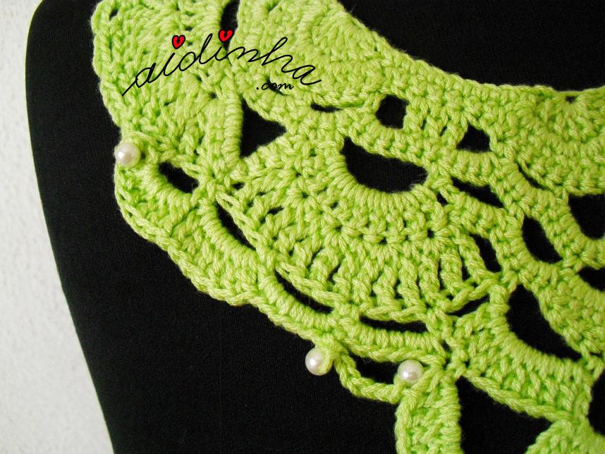 Parte de lado do colar de crochet verde, com pérolas