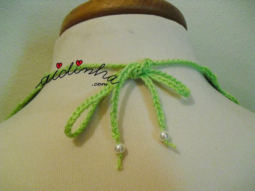 Parte detrás do colar de crochet verde, com pérolas