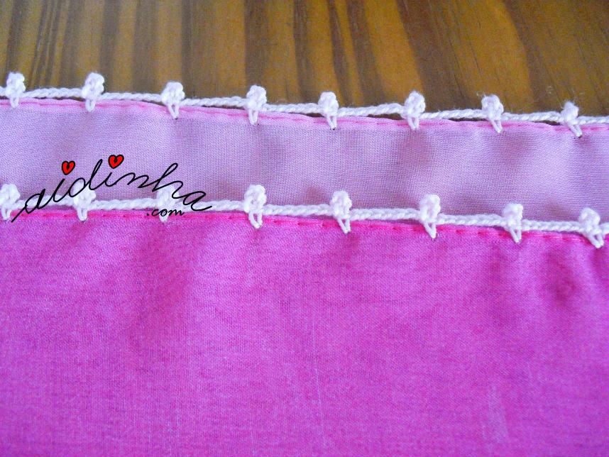 Biquinhos e correntinhas nos lados da écharpe rosa