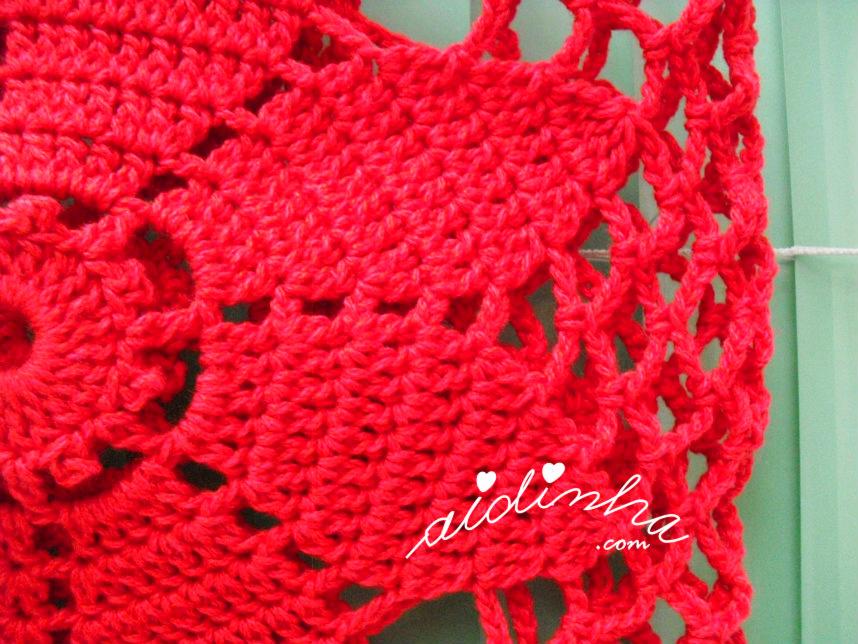 Vista de um dos lados da bolsa vermelha de crochet