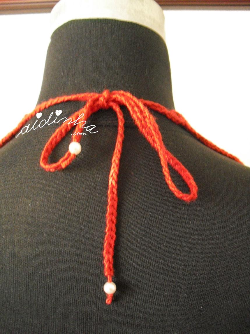 Parte detrás do colar de crochet, vermelho com pérolas
