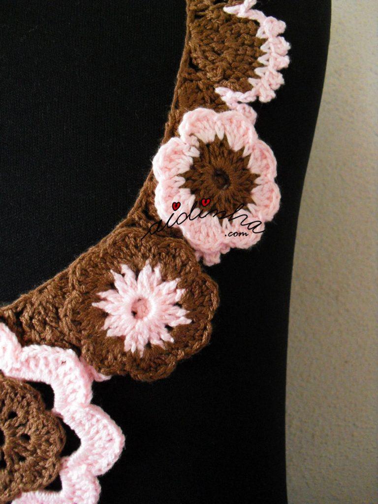 Pormenor das flores rosa e castanho do colar de crochet