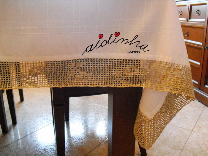 Foto do canto da toalha de mesa com crochet em volta